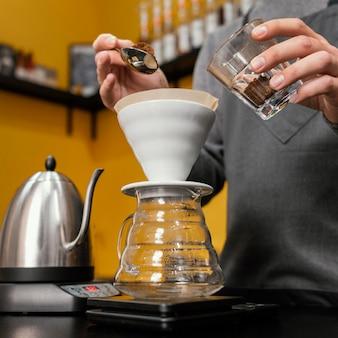 Ángulo bajo de barista macho poniendo café en el filtro
