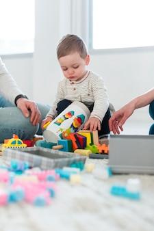 Ángulo bajo de bebé jugando en casa con los padres.