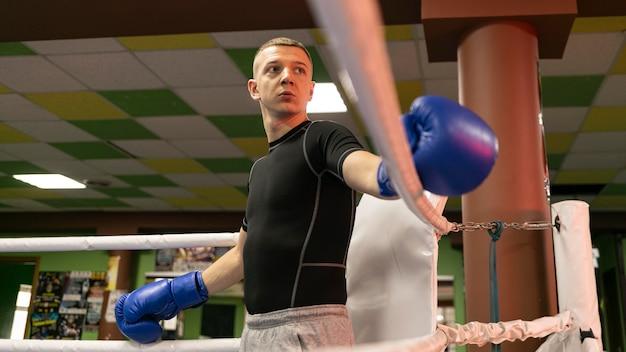 Ángulo bajo de boxeador masculino con guantes en el ring