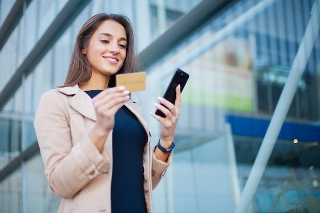 Ángulo bajo de chica contenta de pie en el hall del aeropuerto. está usando la tarjeta de crédito gold y el teléfono celular para pagar
