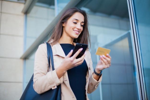 Ángulo bajo de la chica contenta de pie en el hall del aeropuerto. está usando la tarjeta de crédito gold y el teléfono celular para pagar