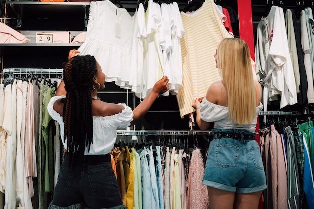 Ángulo bajo chicas jóvenes comprobando la tienda de ropa
