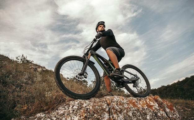 Ángulo bajo de ciclista masculino deportivo montando bicicleta de montaña electrónica y observando el entorno desde la colina pedregosa contra el cielo nublado
