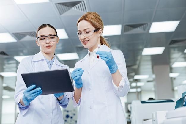 Ángulo bajo. científicos bastante jóvenes que mantienen una sonrisa en los rostros de pie en el laboratorio mientras examinan la sangre