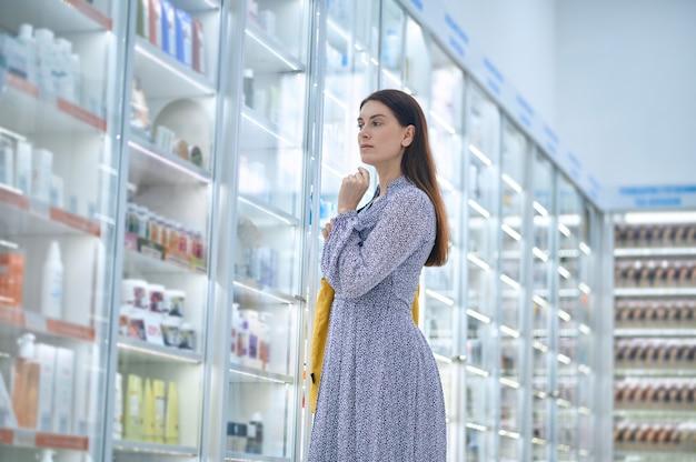 Ángulo bajo de una clienta seria enfocada de pie junto a la vitrina de la farmacia
