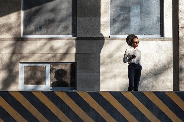 Ángulo bajo elegante mujer con café al aire libre
