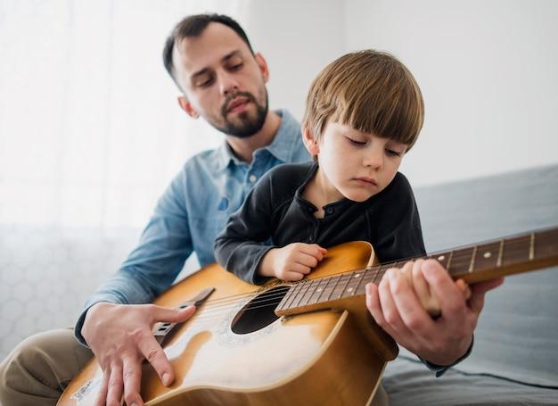 Bajo ángulo de enseñanza de guitarra con niño