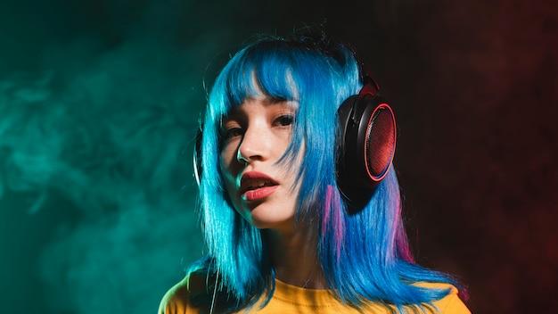 Bajo ángulo femenino dj en club con auriculares