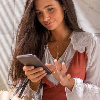 Ángulo bajo de hermosa mujer con smartphone
