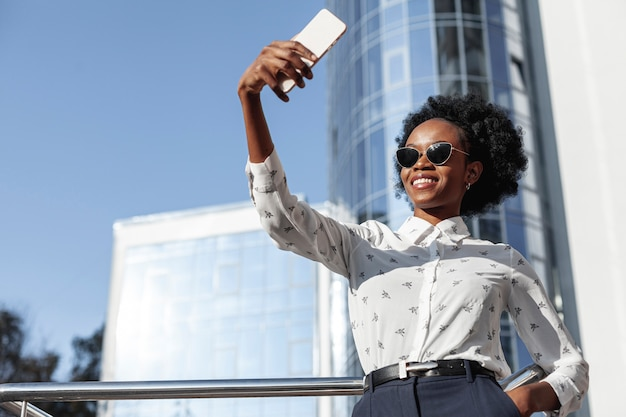 Ángulo bajo hermosa mujer tomando selfies