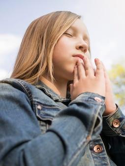 Ángulo bajo de hermosa niña rubia rezando