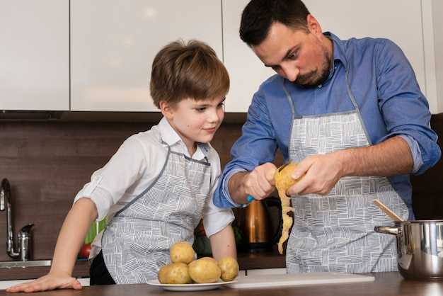 Bajo ángulo hijo y papá limpiando papas