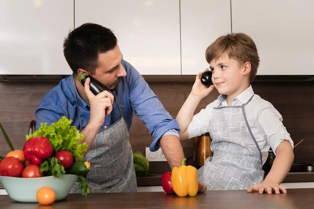 Ángulo bajo juguetón padre e hijo en la cocina