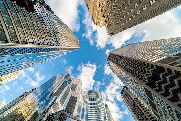 Ángulo levantado con escena de ojo de pez del rascacielos del centro de chicago con reflejo de nubes entre edificios altos