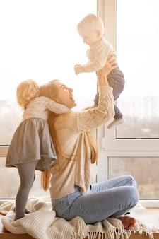 Ángulo bajo mamá jugando con niños