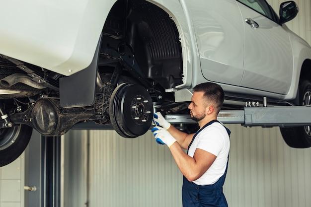 Bajo ángulo mecánico macho revisando las ruedas del coche