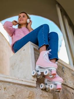 Ángulo bajo de mujer escuchando música en patines