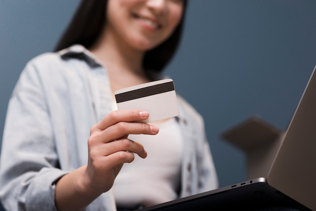 Ángulo bajo de mujer ordenando en línea con tarjeta de crédito