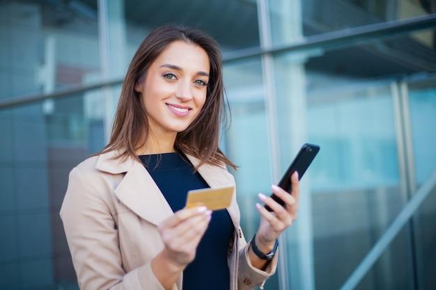 Ángulo bajo de niña complacida de pie en el hall del aeropuerto, está usando una tarjeta de crédito dorada y un teléfono celular para pagar