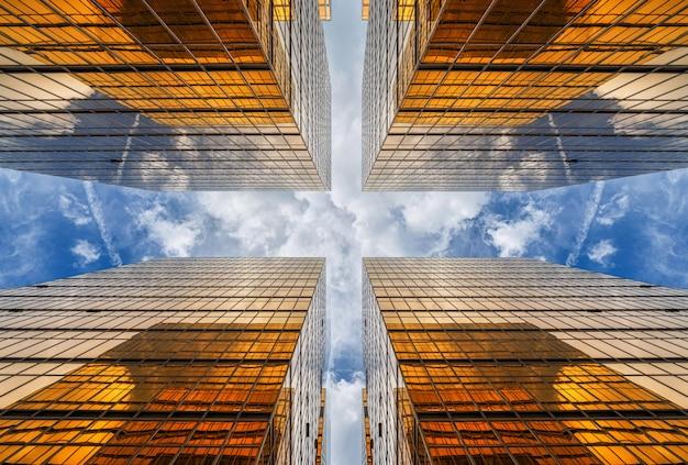 Ángulo no levantado del rascacielos de hong kong con reflejo de nubes entre edificios altos, construcción de gafas