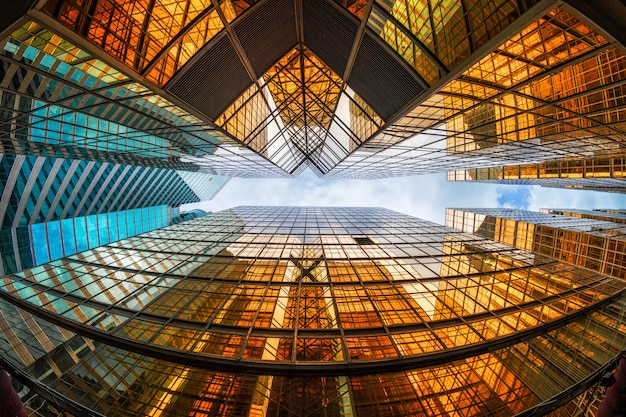 Ángulo no levantado del rascacielos de hong kong con reflejo de nubes entre edificios altos, vidrios de construcción, concepto comercial y financiero, arquitectura e industrial.