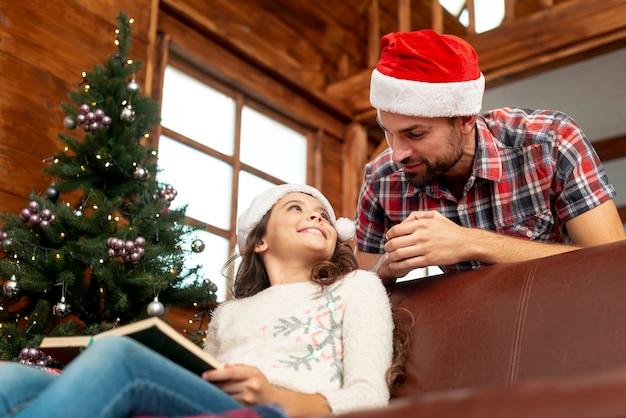 Ángulo bajo padre e hija con libro