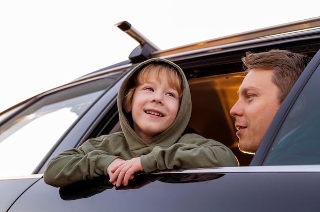 Ángulo bajo de padre e hijo en el coche en un viaje por carretera