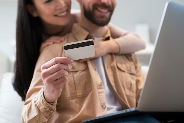 Ángulo bajo de la pareja que compra en línea mientras sostiene la tarjeta de crédito