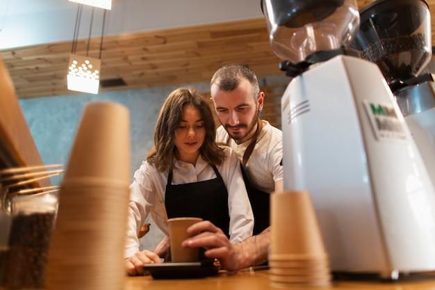 Ángulo bajo de pareja trabajando y haciendo café