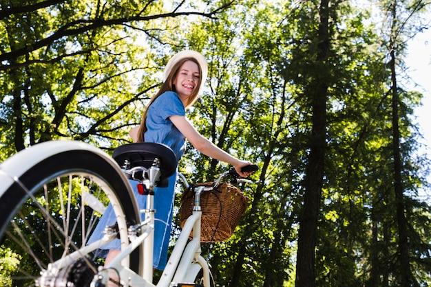 Ángulo bajo sonriente mujer con bicicleta