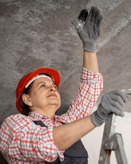 Ángulo bajo de trabajadora de la construcción con casco y guantes