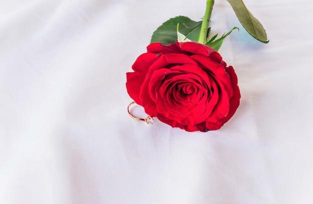 Anillo de boda con rosa roja en mesa de luz.