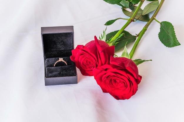 Anillo de boda con rosas rojas en mesa blanca.