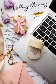 Anillo de bodas en laptop y papeles de invitación