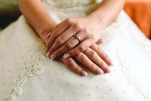 Anillo de bodas en manos de una mujer con su vestido de novia.