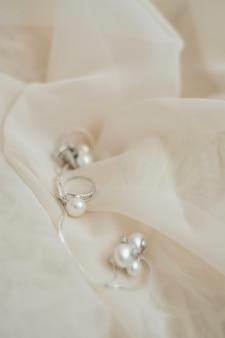 Anillo de bodas perla fondo pastel rosa tela
