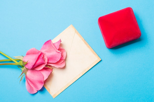 Anillo en una caja con un sobre y rosas sobre un fondo azul