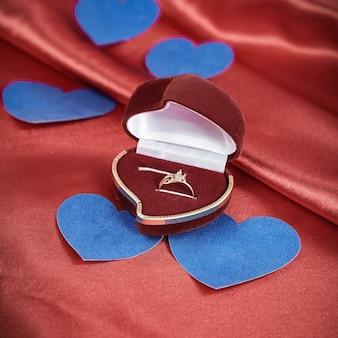 Anillo con un diamante sobre un fondo rojo.