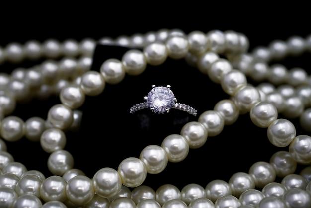 Anillo de diamantes de cristal blanco y cuentas de collar de perlas brillantes blancas.