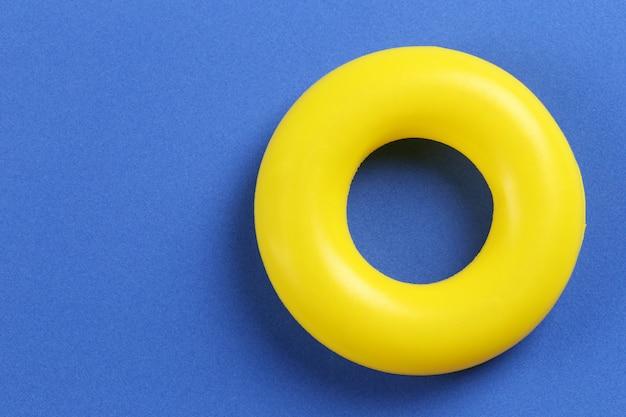 Anillo de goma amarillo colocado sobre un fondo de papel azul.