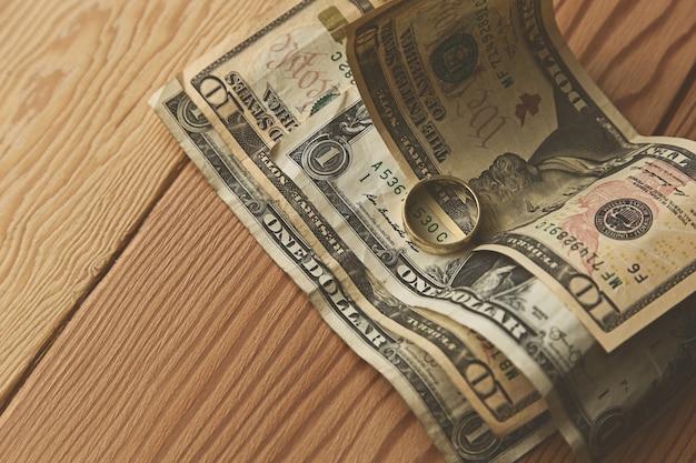 Anillo de oro en algunos billetes de un dólar sobre una superficie de madera