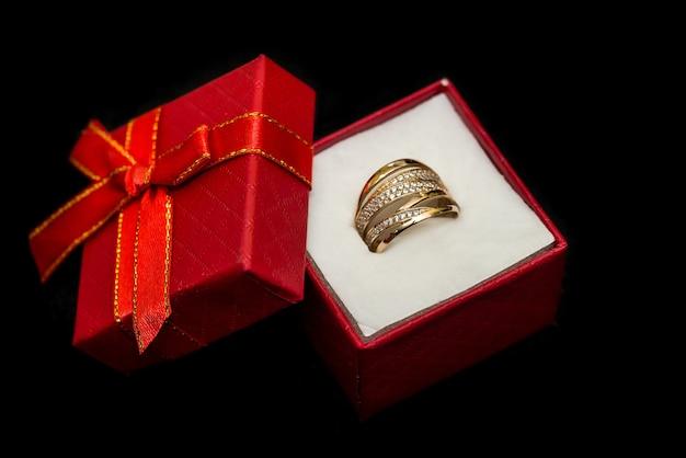 Anillo de oro en caja de regalo roja aislado en negro
