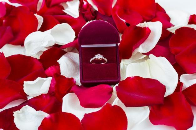 Anillo de oro en una caja de terciopelo con pétalos de rosas blancas y rojas.