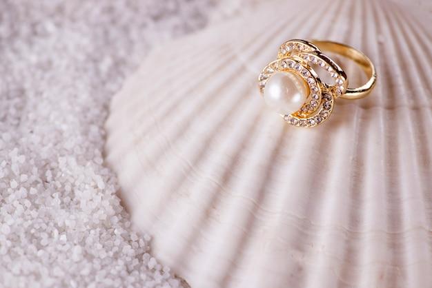 Anillo de oro y concha de mar.