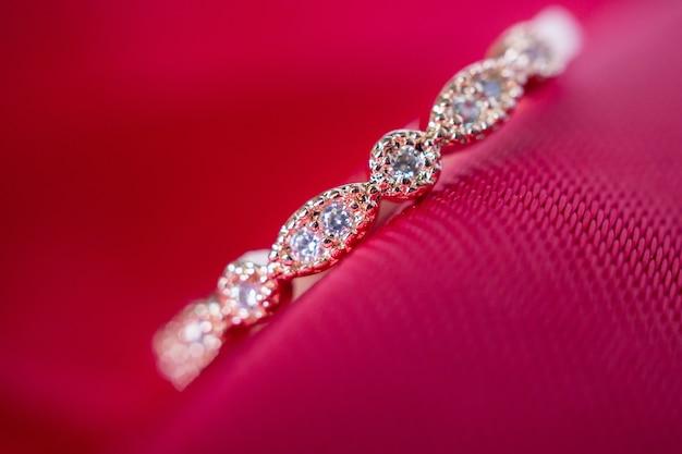 Anillo de oro rosa de lujo de joyería con piedras preciosas de zafiro sobre fondo de textura de tela roja
