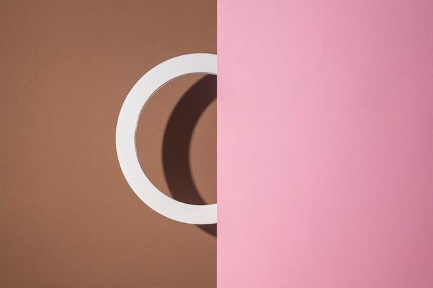 Un anillo de podio redondo se asoma de cartón rosa sobre un fondo marrón