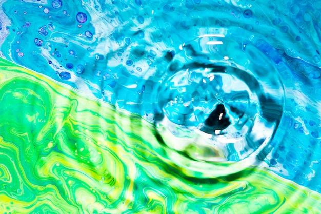 Anillos de agua de primer plano sobre fondo verde y azul