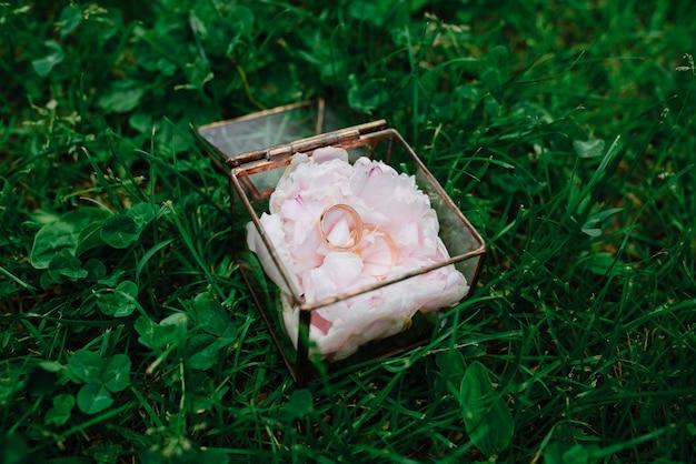 Anillos de boda en una caja de cristal vintage sobre una almohada de peonía