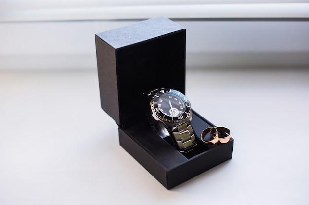 Anillos de boda en una caja de relojes, relojes de pulsera, relojes de bolsillo, hora, signo infinito de los anillos, anillos de boda