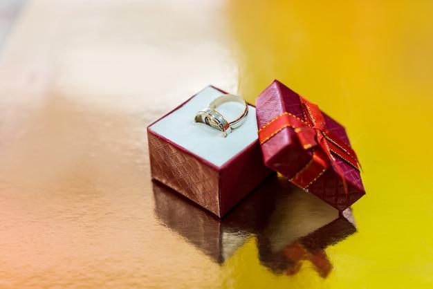Anillos de boda en caja roja actual sobre fondo dorado